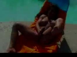 امرأة سمراء الآسيوية العضلات مستلقية على السرير وامتصاص عصا اللحوم الدهنية، مثل عاهرة
