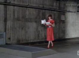 امرأة ذات شعر أحمر حصلت على القصب أمام مكان حريق، في منزلها الضخم