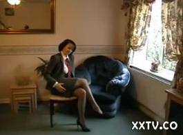 امرأة أنيقة مع ثقب السرة ملقاة على الأريكة وفرك لعبة الجنس ضخمة